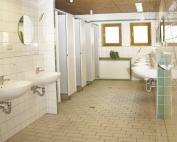 Waschraum mit Waschbecken und Einzelwaschkabinen